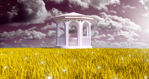 The field of gold in Paradise. White wood gazebo in the silence of gold grain field Stock Photos