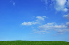 Field of grass with blue sky. Green hilltop with blue cloudy sky background. Copy Space. Summertime concept Royalty Free Stock Images