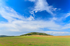 Field of grass, hill and perfect sky Royalty Free Stock Images
