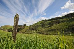 Field with grass, hils, fence post and sky Royalty Free Stock Photo