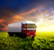 Field of grass and truck. Field of grass in sunset and truck Royalty Free Stock Photography