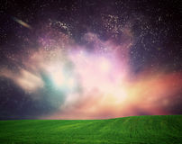 Field of grass under dream galaxy sky, space, glowing stars. Green field of grass under dream galaxy sky, space. Glowing stars, universe light Stock Images