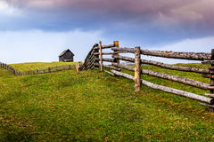 Field of green with wooden house on the hill Stock Image
