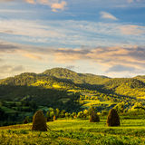Field with haystack on hillside at sunrise Stock Images
