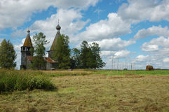 Field with haystacks and wooden church Stock Photography