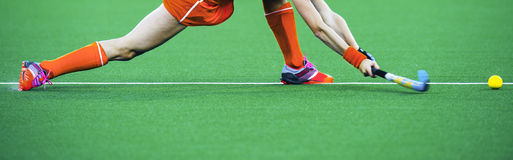 Field hockey banner. Female athlete field hockey player performing a stretched drag flick on an artificual grass pitch Stock Photos