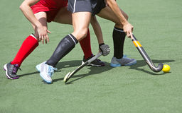 Field hockey close up. Close up of two field hockey players, challenging eachother for the control and posession of the ball during an intense, competitive match Royalty Free Stock Photos