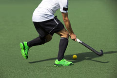 Field Hockey. Player, in possesion of the ball, running over an astroturf pitch, looking for a team mate to pass to Stock Images