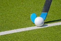Field hockey stick and ball on green grass.  stock photos
