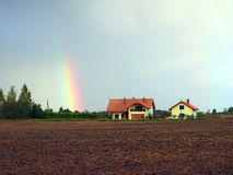 Field, homestead and rainbow, Lithuania stock images