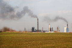 The field with industrial plant in the background Royalty Free Stock Image