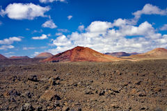 Field of lava volcanic bombs stones against the background of red volcano hill of Timanfaya National Park Royalty Free Stock Images