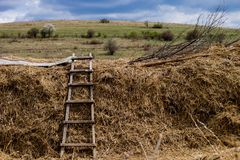 Ladder in the fields under the cloudy sky stock photos