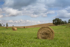 The field with many haystacks under gray and blue skies with beautiful clouds. The field in front is gree, but on the back side is sloping field Stock Photos