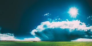 Field Or Meadow Landscape With Green Grass Under Scenic Spring Blue Dramatic Sky With White Fluffy Clouds. Rain Clouds stock images