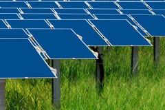 Field med många sol- celler på grönt gräs Arkivbild