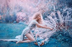 Field mermaid collects herbs and flowers in small basket. slender forest nymph sits on her knees in long light dress