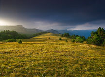 Field and mountains at sunset. A landscape view across an open field at sunset with mountains in the background Royalty Free Stock Image