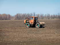 In field is moving an old tractor Royalty Free Stock Images