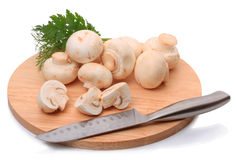 Field mushrooms on a cutting board and knife Royalty Free Stock Image