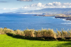 Field at the ocean coast, Azores, Portugal. View to the green field, town and mountains at the Atlantic ocean coast, San Miguel, Azores, Portugal Stock Image