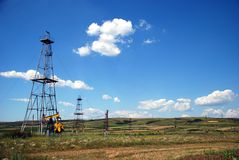 A field with oil. Derrick's Stock Images