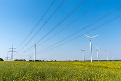 Field of rapeseed with high-voltage lines and wind turbines royalty free stock images