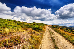 Field road in the mountains under the blue sky. Dramatic scene. Royalty Free Stock Photography