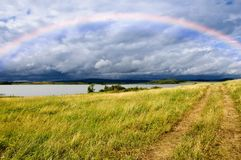 Field road and rainbow over lake Royalty Free Stock Photography