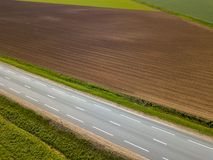 Spring arable land. A field and  road. View from above. A field and  road. Spring arable land.  Aerial view from above Stock Photography