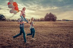 Field running family. With balloons and kite royalty free stock images