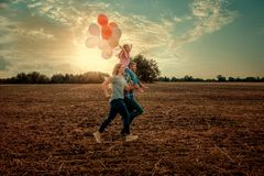 Field running family. With balloons and kite royalty free stock photography