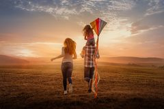 Field running family. With balloons and kite royalty free stock image