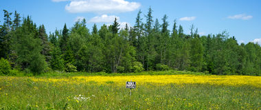 Field with small no trespassing sign Stock Photo