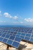 Field of solar collectors near sea with blue sky Stock Image