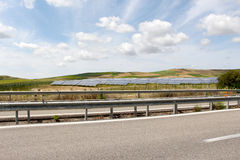 Field of solar panels, dramatic sky. An overall view of some hills and vineyards with a field of solar panels, an empty road in the foreground, under a dramatic Stock Photo