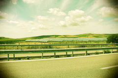 Field of solar panels, vintage stile, dramatic sky. An overall view of some hills and vineyards with a field of solar panels, an empty road in the foreground royalty free stock image