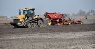 In the field sow peas. Chortkiv - Ternopil - Ukraine - April 10, 2018. At the spring field of the agrarian firm `Dzvin` using a crawler tractor CAT Challenger Stock Images