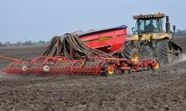 In the field sow peas. Chortkiv - Ternopil - Ukraine - April 10, 2018. At the spring field of the agrarian firm `Dzvin` using a crawler tractor CAT Challenger Royalty Free Stock Photography