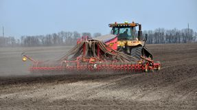In the field sow peas. Chortkiv - Ternopil - Ukraine - April 10, 2018. At the spring field of the agrarian firm `Dzvin` using a crawler tractor CAT Challenger Stock Image