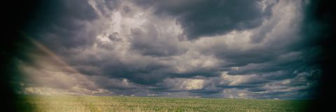 Field and storm clouds. Banner for design. Field and storm clouds. Summer season. Rural landscape. Banner for design royalty free stock images
