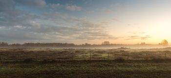 Field in the sunrise in the town of Blaricum. Sunrise over a field in the Netherlands with a colorful sky stock photos