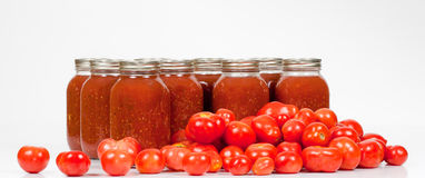 Field Tomatoes with Jars of Canned Tomato Sauce. A front studio shot of fresh organic field tomatoes lying in front of homemade canned tomato sauce jars Stock Photography