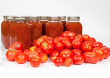 Field Tomatoes and Tomato Sauce. A front studio shot of fresh organic field tomatoes lying in front of homemade canned tomato sauce jars Royalty Free Stock Photography