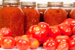 Field Tomatoes with Tomato Sauce. Close up studio shot of some organic field tomatoes with mason jars filled with freshly homemade tomato sauce Royalty Free Stock Image