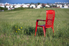 Field Tranquility. Red plastic chair in the middle of oats field on a spring sunny day. A small island of tranquility in the middle of hustling and bustling city Stock Photography