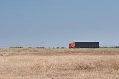 A field and a truck passing on the highway Royalty Free Stock Photography