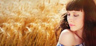 A field of wheat. Beautiful woman. Field of wheat. Beautiful woman. Ears of Golden wheat closeup. Rural landscapes. Backdrop of ripening ears of wheat field. Of Stock Photo