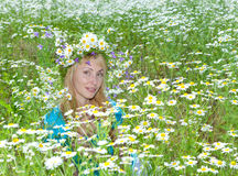 Field of white flowers and the smiling young woman in a wreath Stock Photography