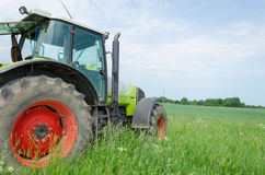 Field work tractor in meadow. Season of field work heavy equipment tractor stands in meadow Royalty Free Stock Photos